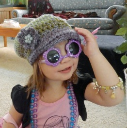 newsboy style crochet hat with flower accent in green and purple.